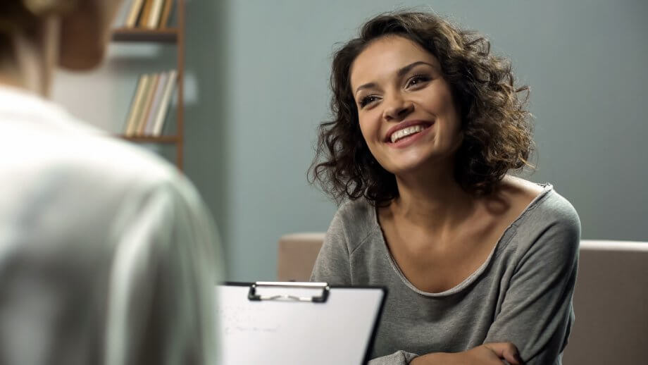 Woman with short brown curly hair smiling at a doctor holding a clipboard in an office setting.